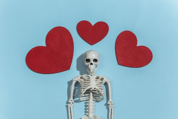 Skeleton and red decorative hearts on a bright blue background. valentine's day or halloween theme.