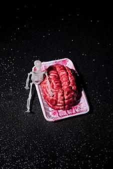 Skeleton sit besides a brain composition