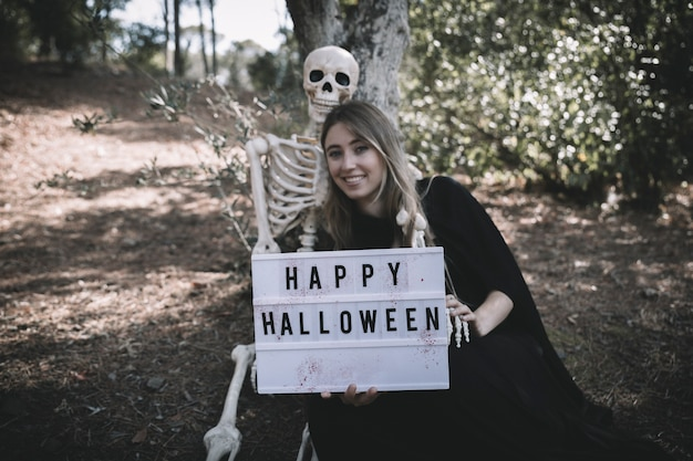 Skeleton sitting near smiling lady with tablet