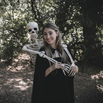 Skeleton standing behind laughing happy lady