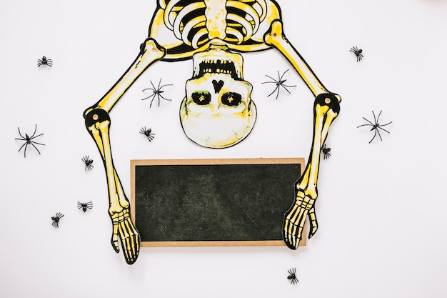 Skeleton surrounded by spiders holding board