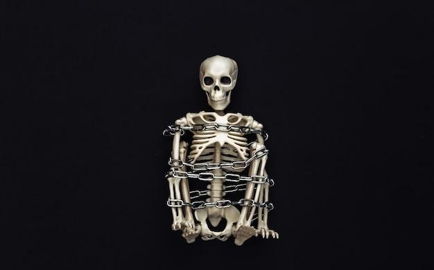 黒に金属チェーンで包まれたスケルトン。ハロウィーンの装飾、怖いテーマ