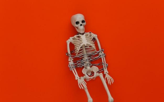 Skeleton wrapped in metal chain on orange. halloween decoration, scary theme