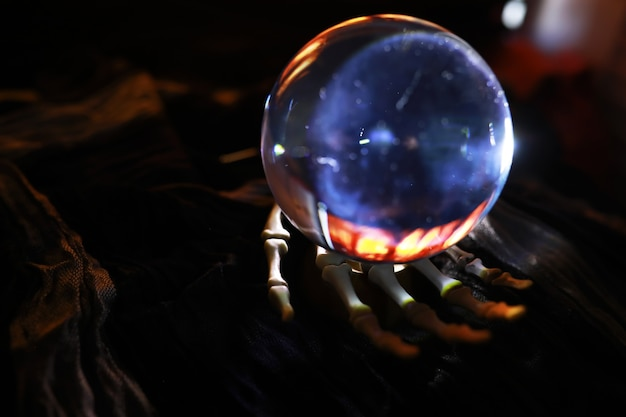 Skeleton zombie hand rising out of a graveyard - halloween. mysterious magic ball predictions and smoke on dark scene. fortune teller, mind power, prediction concept. mysterious background