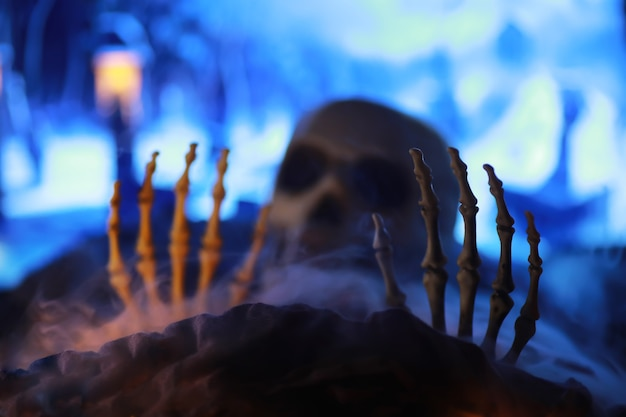 Skeleton zombie hand rising out of graveyard - halloween