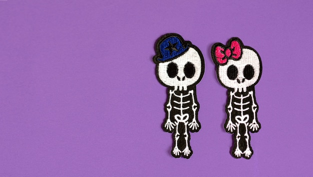 Skeletons of a boy and a girl on a purple background, concept of halloween and the day of the dead mexican holiday