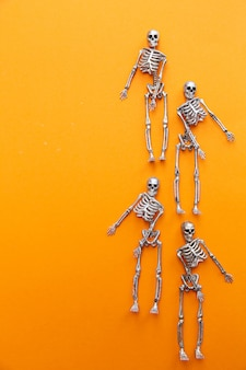 Skeletons dancing on an orange table