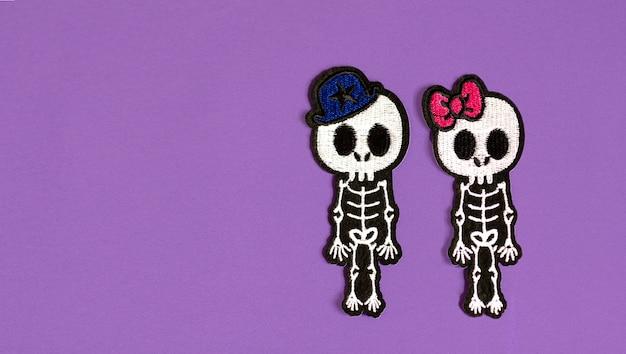 보라색 배경에 소년과 소녀의 해골, 할로윈의 개념과 죽은 멕시코 휴일의 날