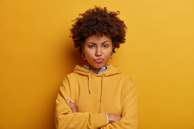 Skeptic angry ethnic woman expresses suspision, stands with arms folded, pouts lips and waits for explanations, being angry with someone, wears casual clothes, isolated on yellow wall