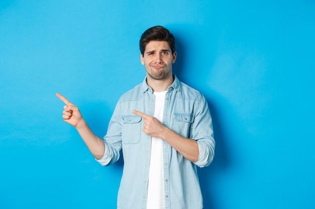 懐疑的な大人の男が指を左に向け、疑わしくて不確かに見え、青い背景の上に立っている