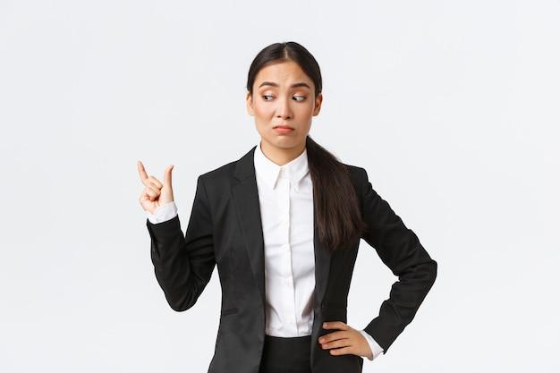 회의적이고 어색한 젊은 아시아 사업가, 작은 것을 형성하고 크기가 실망한 검은 양복을 입은 판매원, 작은 작은 것, 흰 벽 위에 재미없는 찡그린 얼굴.
