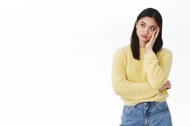 懐疑的で退屈な若いアジア人女性は、イベントに興味がなく、思慮深く疲れて目をそらし、退屈から顔をしかめ、感動せず、暗い白い壁の上に立っています