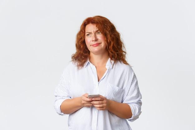 懐疑的で混乱している中年の赤毛の女性は、イライラしたにやにや笑い、携帯電話を持って、奇妙なメッセージを読んで、熟考し、白い壁の上に立っています。