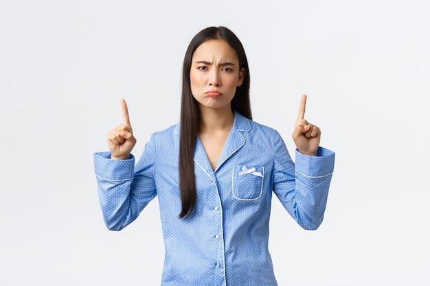 Скептическая и разочарованная азиатская женщина, морщась от неприязни, оценивая что-то плохое, показывая пальцем вверх, надувая губы, жалуясь на ужасное качество продукции, стоя в пижаме над белой стеной