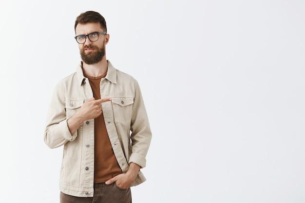 Скептически настроенный и разочарованный бородатый мужчина в очках позирует на фоне белой стены