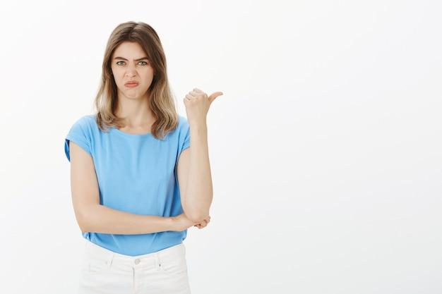 懐疑的で失望した金髪の女性が不平を言って、邪魔なものや悪いものに指を向ける