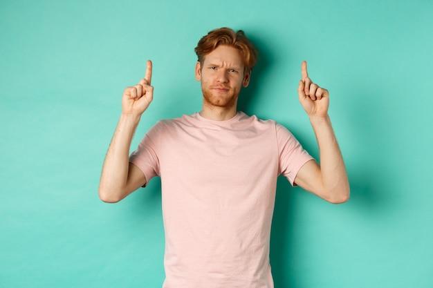 懐疑的で失望した赤毛の男が指を上に向け、眉をひそめ、不機嫌そうに見え、ターコイズブルーの背景の上に立っている