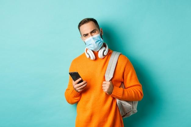 フェイスマスクを身に着けている、バックパックと携帯電話を持って、眉をひそめている、水色の背景の上に立っている懐疑的で失望した若い男。