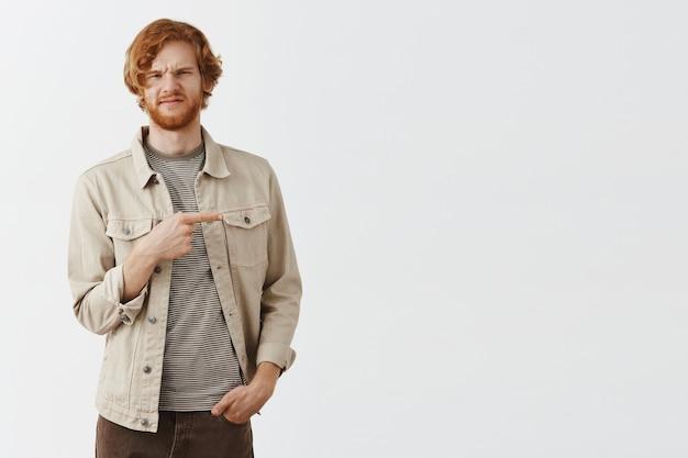 白い壁に向かってポーズをとる懐疑的で不快なひげを生やした赤毛の男