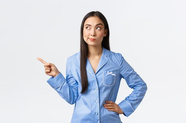 Скептически и недовольно симпатичная азиатская девушка в пижаме с ухмылкой разочарована
