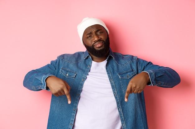 회의적이고 의심스러운 흑인 남자가 카메라를 즐겁게 쳐다보고, 나쁜 것을 손가락으로 가리키고, 분홍색 배경 위에 서 있습니다.