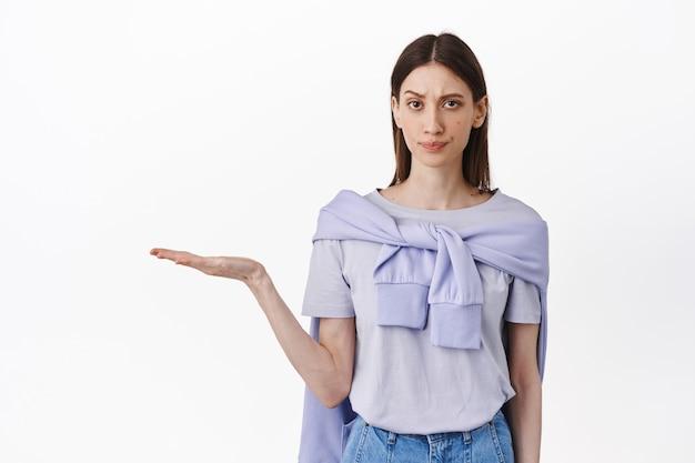 懐疑的で疑わしい女の子が空のスペースの製品を開いた手に持って、疑いと嫌悪感を持って見て、不機嫌に眉をひそめ、購入する悪いアイテムを表示し、白い壁に立ちます