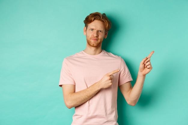 ターコイズブルーの背景の上に立って、不機嫌そうな顔でプロモオファーを示して、右上隅に指を指しているtシャツの懐疑的で疑わしい赤毛の男。