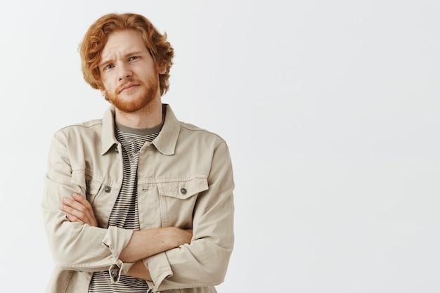 Скептически и неохотно бородатый рыжий парень позирует на фоне белой стены
