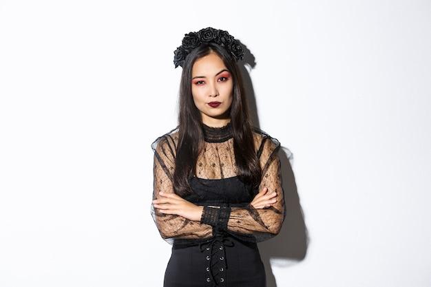 회의적이고 재미없는 아시아 여자는 카메라, 팔 가슴 크로스에 실망 찾고 할로윈 의상을 입고. 검은 고딕 드레스와 화환을 입은 여성.