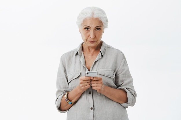 懐疑的で面白くないおばあちゃんが携帯電話を持って見ている