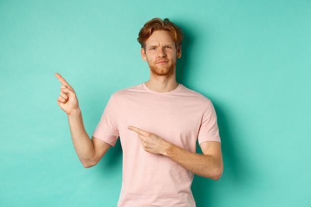 懐疑的で面白くない赤毛の男が眉をひそめ、左上隅のバナーに指を向け、ターコイズブルーの背景の上に立っています。