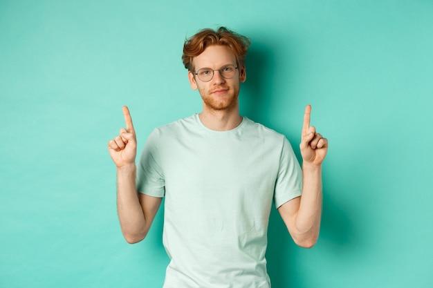 懐疑的で面白くない赤毛の男が眼鏡とtシャツを着て、指を上に向けて役に立たないものを見せ、ミントの背景に立っています。