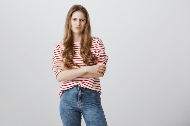 嫌悪感から顔をゆがめた懐疑的で不満の10代の少女