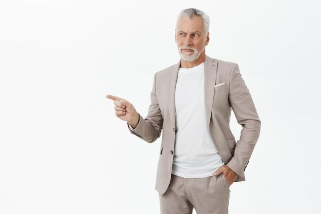 左指を指して顔をゆがめたスーツを着た懐疑的で不確かなビジネスマン