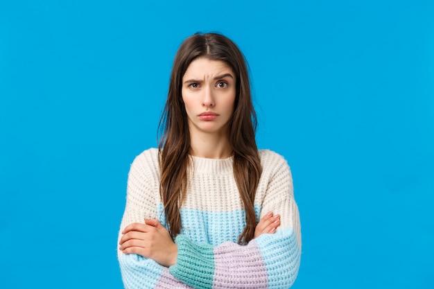 愚かでナンセンスな何かを聞く懐疑的でイライラして不機嫌な若い女性が眉を上げる