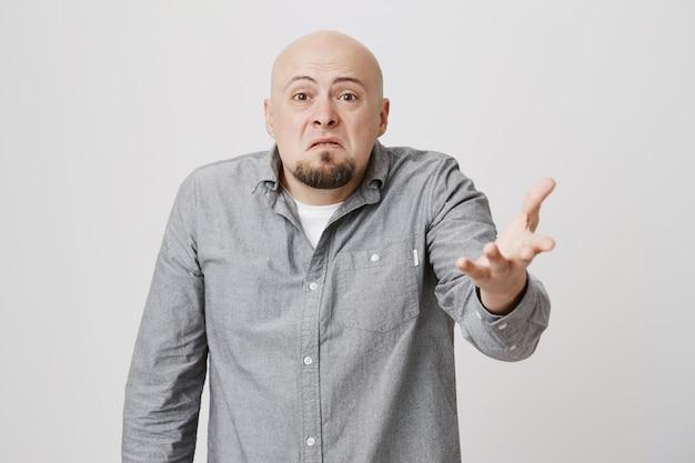 Skeptical annoyed bald man raising hand dismay