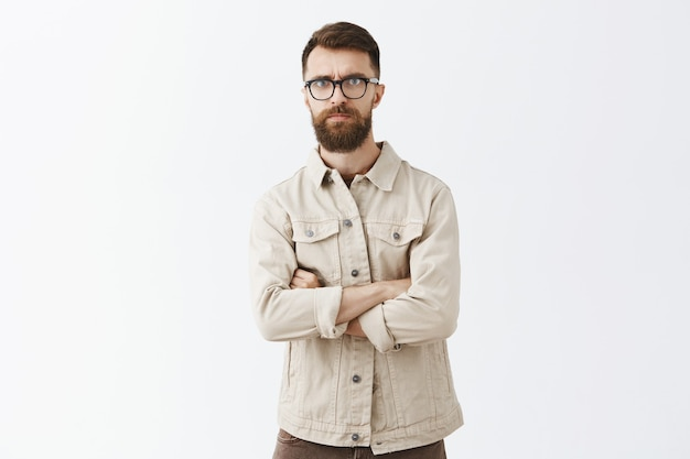 Skeptical bearded man in glasses posing against the white wall