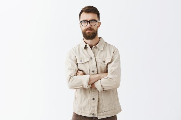 Скептически бородатый мужчина в очках позирует у белой стены