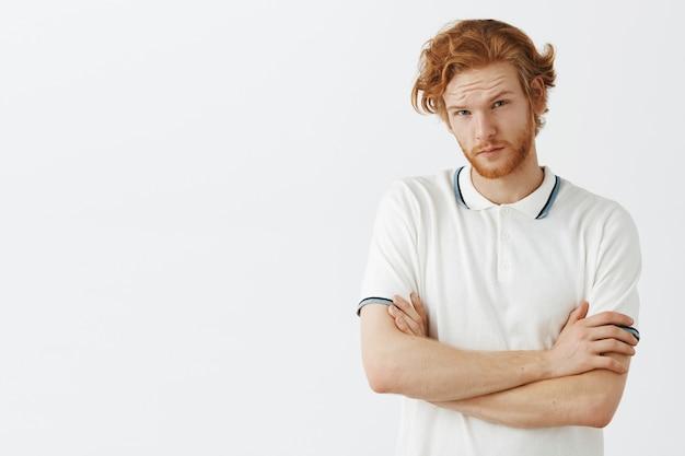 Ragazzo scettico con la barba rossa in posa contro il muro bianco