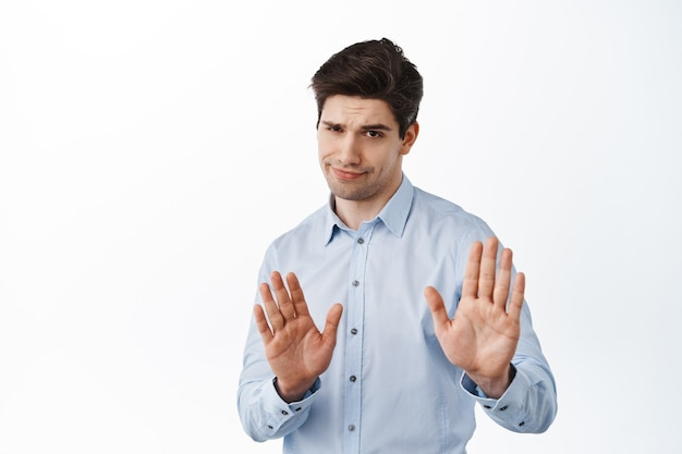 Skeptical boss, male entrepreneur showing refuse, reject block gesture, telling to quit, standing over white wall