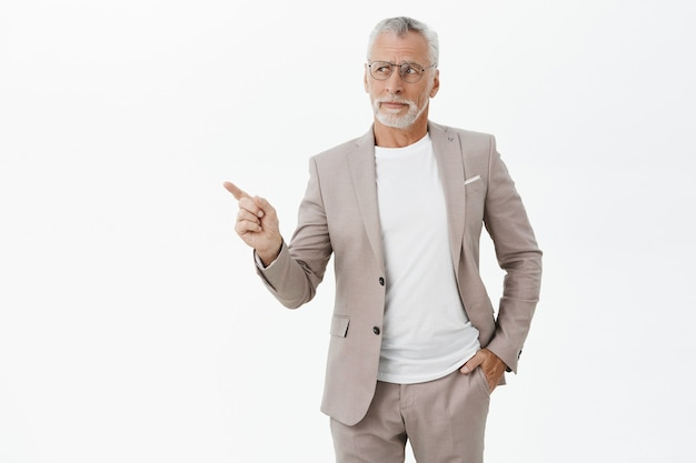 Skeptical businessman in suit and glasses pointing finger left thoughtful
