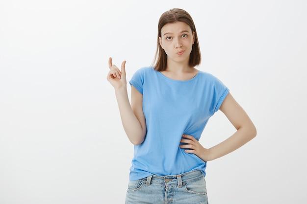 Donna carina scettica che fa il broncio e mostra qualcosa di troppo piccolo, piccola cosa