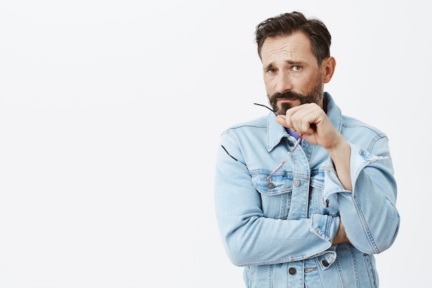 Skeptical and disappointed bearded mature man posing