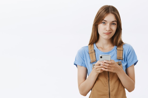 Skeptical and displeased girl smirking unamused, holding mobile phone