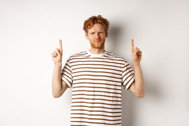 懐疑的なハンサムな赤毛の男が指を上に向け、顔をゆがめ、カメラを疑わしく見て、白い背景の上に優柔不断に立っている