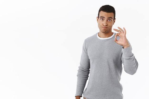 Скептически красивый молодой человек, показывающий нормальный жест, неплохо, впечатлен хорошей работой
