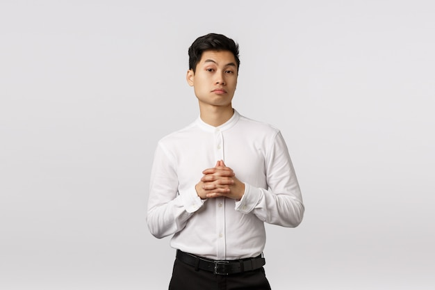 Skeptical and impressed young asian businessman consider something, clench hands together, raising eyebrows pleased, listen interesting offer, have business meeting, standing