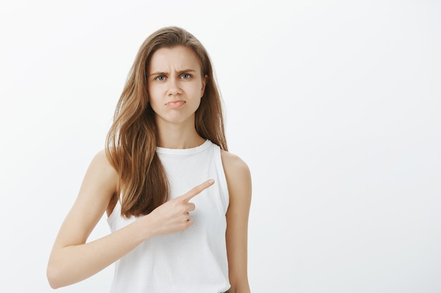 Skeptical and judgemental girl don't recommend product, pointing right and grimacing disappointed