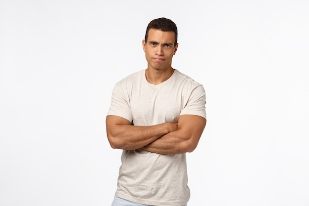 Skeptical and judgemental serious-looking handsome strong man with huge biceps