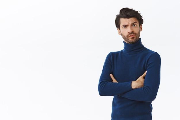 Скептичный, сумасшедший, серьезного вида брюнет с бородой в свитере с высоким воротом, скрестив руки на груди, ухмыляется и хмурится, смотрит в камеру раздраженно, ждет опоздания друга, стоит у белой стены